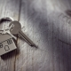 House key on a house shaped keychain resting on wooden floorboards concept for real estate, moving home or rental property