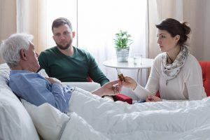 Old man laying in bed with son and daughter attending to him Advance Care Planning